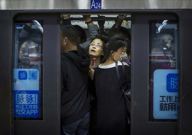 Chinese commuters crowd onto a subway car on the metro during rush hour on October 16, 2014 in Beijing, China. (Photo by Kevin Frayer/Getty Images)