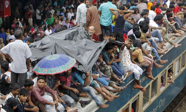 People shelter under a sheet of plastic as they crowd on top of a train as it enters the Dhaka airport rail station September 24, 2015, as thousands of Bangladeshi Muslims head home to celebrate Eid-al-Adha. (Photo by Ashikur Rahman/Reuters)