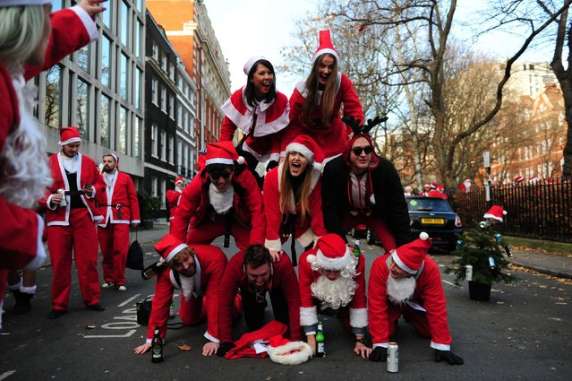 These Santas strike a pose in the middle of London during Santacon day in London, England, on December 9, 2017. (Photo by PA Wire)