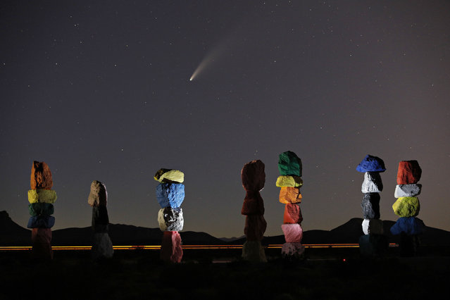 "The comet Neowise, or C/2020 F3, is seen in the evening sky above the artwork titled: ""Seven Magic Mountains"" by artist Ugo Rondinone, Thursday, July 16, 2020, near Jean, Nev., south of Las Vegas. (Photo by John Locher/AP Photo)"