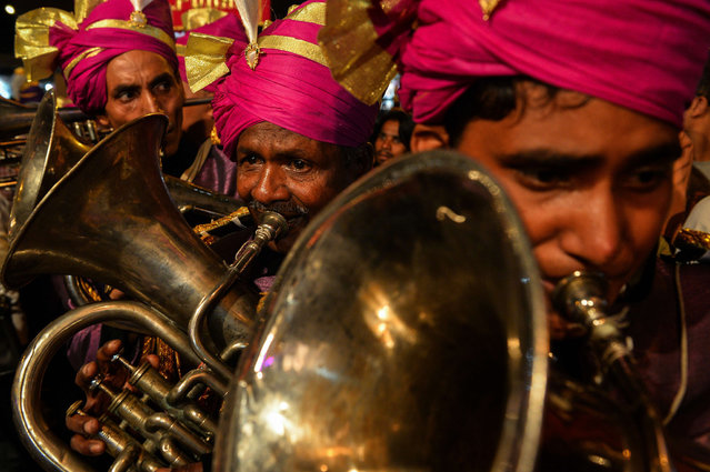 Members of an Indian wedding band play brass instruments during a religious procession for the Hindu festival Ganesh Chaturthi in New Delhi on September 24, 2015. (Photo by Chandan Khanna/AFP Photo)