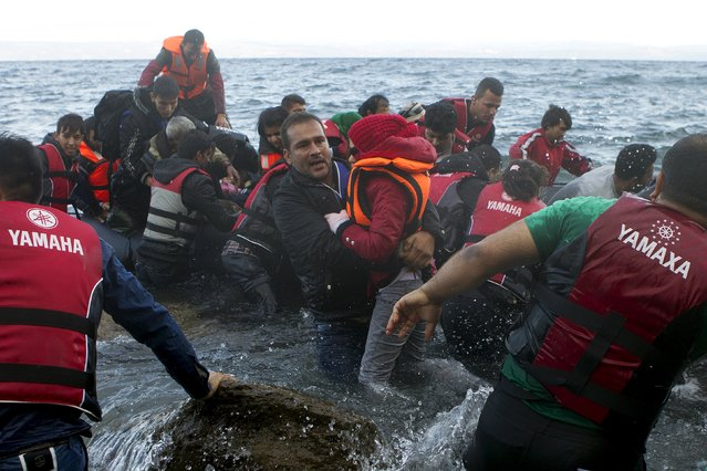A migrant man pulls a girl out of the water as refugees and migrants arrive on an overcrowded dinghy in rough sea on the Greek island of Lesbos, after crossing a part of the Aegean Sea from the Turkish coast, October 2, 2015. (Photo by Dimitris Michalakis/Reuters)