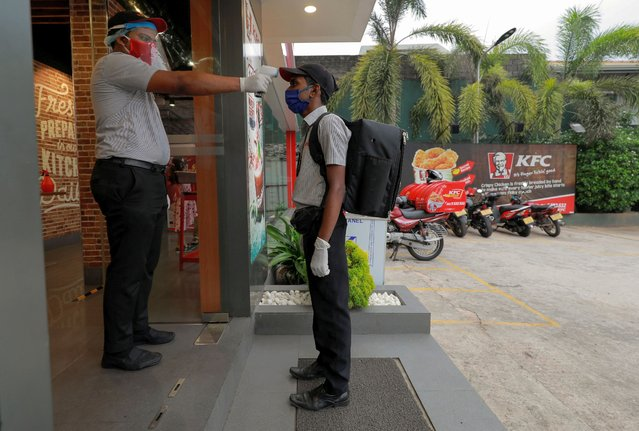 A delivery staff member wearing a protective mask is checked with a thermal scanner at the main entrance of a KFC fast food outlet, amid concerns about the spread of the coronavirus disease (COVID-19), in Colombo, Sri Lanka, July 9, 2020. (Photo by Dinuka Liyanawatte/Reuters)