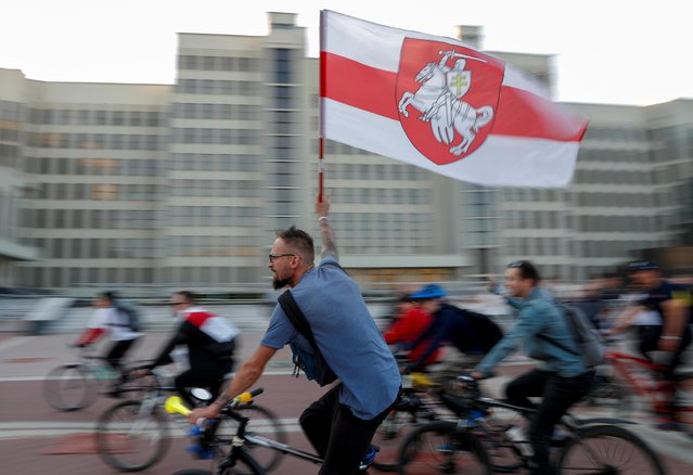 A man rides a bicycle carrying a flag at the Independence Square during an opposition demonstration against presidential election results in Minsk, Belarus on August 22, 2020. (Photo by Vasily Fedosenko/Reuters)