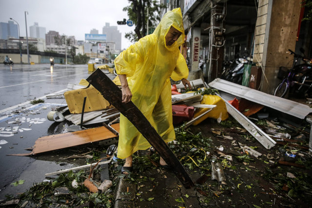 A man salvages usable materials from debris after strong winds and rain from Super Typhoon Meranti in Kaohsiung, southern Taiwan, 14 September 2016. (Photo by Ritchie B. Tongo/EPA)