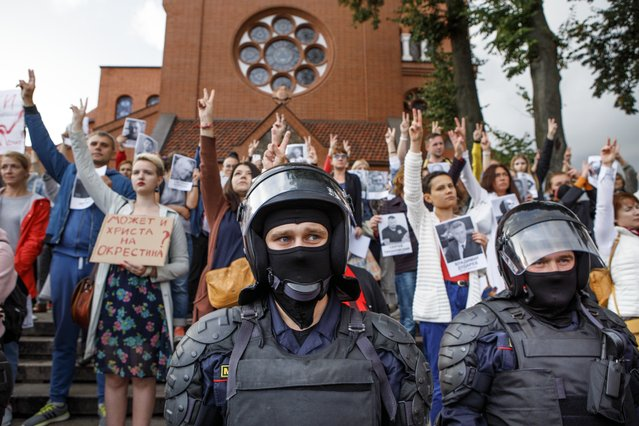 Riot police block protesters in front of a Catholic church in Minsk, Belarus, Thursday, August 27, 2020. Police in Belarus have dispersed protesters who gathered on the capital's central square, detaining dozens. (Photo by Dasha Sapranetskaya/AP Photo)