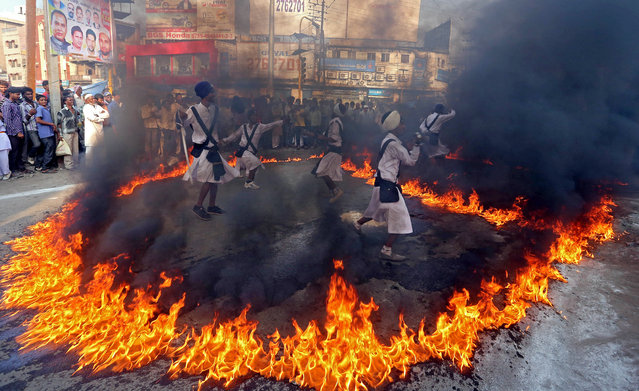 Sikh devotees show their skills of martial art in fire ring during a religious procession taken out to mark the birth anniversary of first Sikh Guru or master Sri Guru Nanak Dev Ji, the founder of Sikhism in Bhopal, India November 3, 2014. The birth anniversary of the first Sikh Guru will be observed on November 6. (Photo by Sanjeev Gupta/EPA)