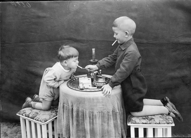 Two young boys kneel on stools on either side of a round table as one uses a match to this the other's cigarette, November 12, 1928. (Photo by FPG/Getty Images)