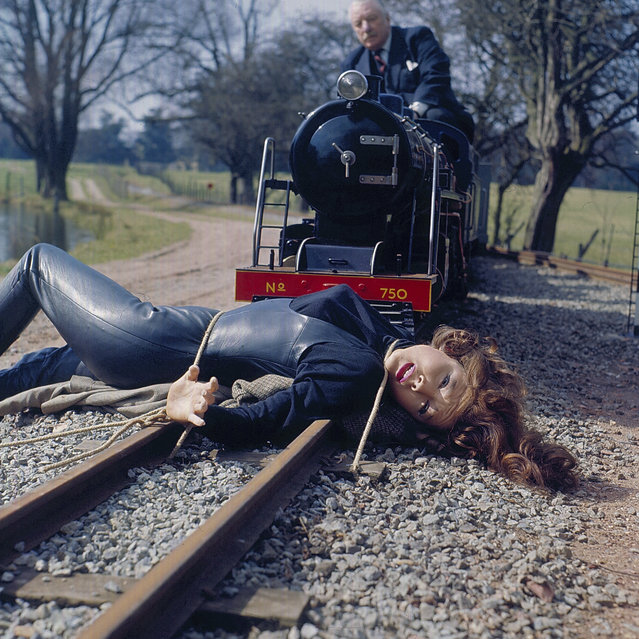 "English actress Diana Rigg as ""Emma Peel"" is tied to a railway track as a miniature train advances on her in a scene from the television series ""The Avengers"" in 1968. Rigg died at her home in London on 10 September 2020, at the age of 82. (Photo by Popperfoto via Getty Images/Getty Images)"