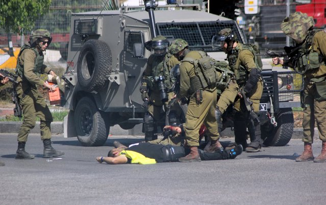 A Palestinian posing as a journalist, who stabbed an Israeli soldier with a knife, lies on the ground after being shot dead near the West Bank city of Hebron October 16, 2015. (Photo by Jameel Salhab/Reuters)