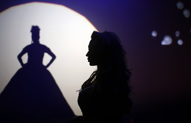 In this Sunday, September 18, 2016 photo, Britanie Eichenholc, from France, right, is seen silhouetted during her performance at the Miss Trans Star International 2016 show celebrated in Barcelona, Spain. (Photo by Manu Fernandez/AP Photo)