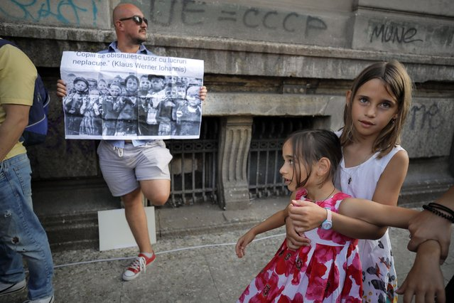 """Children play next to a man holding a banner showing children in a concentration camp and a paraphrase from a statement by Romanian President Klaus Iohannis that reads """"Children get used to unpleasant things easily"""" during a protest in Bucharest, Romania, Saturday, September 19, 2020. (Photo by Vadim Ghirda/AP Photo)"""