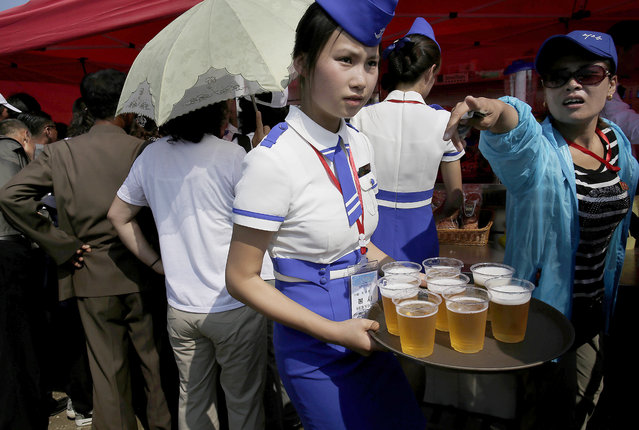 A waitress serves beers during an air festival on Saturday, September 24, 2016, in Wonsan, North Korea. (Photo by Wong Maye-E/AP Photo)