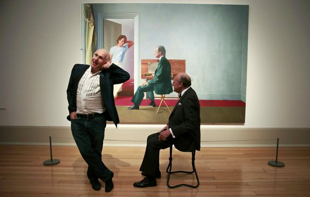 """Ballet dancer Wayne Sleep (L) and book dealer George Lawson pose in front of """"George Lawson and Wayne Sleep"""" by David Hockney at Tate Britain in London, Britain October 19, 2015. A recent gift from Hockney for Tate's collection, this is the first time the celebrated portrait has been shown in Britain. (Photo by Suzanne Plunkett/Reuters)"""