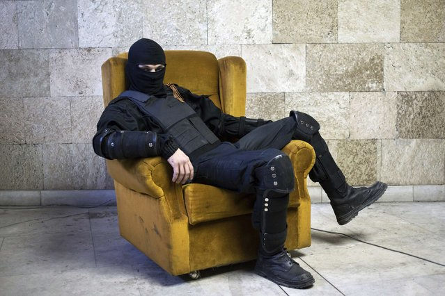 A masked pro-Russian protester sits on a chair as he poses for a picture inside a regional government building in Donetsk, eastern Ukraine in this April 25, 2014 file photo. On March 3, a couple hundred pro-Russian demonstrators stormed the Donetsk regional government building after clashing with police who were guarding the main entrance. (Photo and caption by Marko Djurica/Reuters)