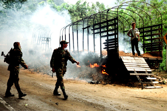 Two colombian soldiers patrol in front at a truck burned by rebels of the Revolutionary Armed Forces of Colombia (FARC) in Cisneros, 80 km west from Cali, Valle del Cauca province March 6, 2002. (Photo by Reuters/Stringer)