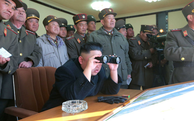 North Korean leader Kim Jong-un (C) and military officers watch a live shell firing drill to examine war fighting capabilities of artillery sub-units, whose mission is to strike DaeYeonpyeong island and Baengnyeong island of South Korea, in the western sector of the front line in this picture released by the North's official KCNA news agency in Pyongyang, on March 14, 2013. (Photo by KCNA via Reuters)