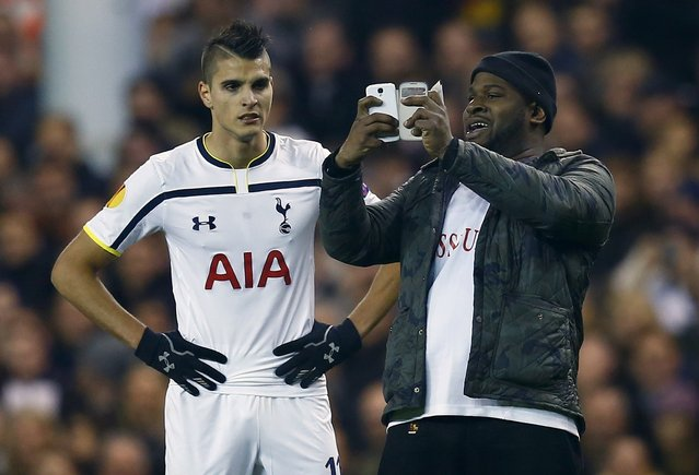 """A spectator runs onto the pitch and takes a """"selfie"""" of himself and Tottenham Hotspur's Erik Lamela (L) during their Europa League soccer match against Partizan Belgrade at White Hart Lane in London November 27, 2014. (Photo by Eddie Keogh/Reuters)"""