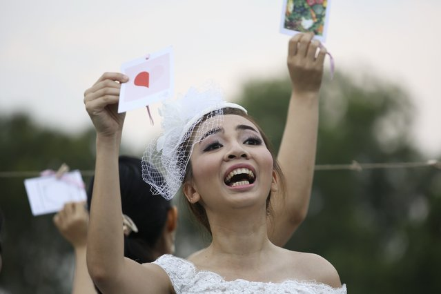 """A woman gestures to her fiance during the """"Running of the Brides"""" race in a park in Bangkok November 29, 2014. (Photo by Damir Sagolj/Reuters)"""