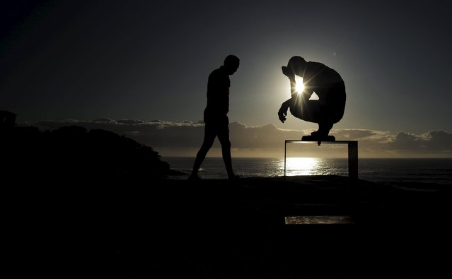 "The sun rises over the Pacific Ocean, behind a bronze sculpture by British artist Laurence Edward titled ""Crouching Man"", during the 19th annual Sculpture by the Sea exhibition in Sydney, Australia October 24, 2015. (Photo by Jason Reed/Reuters)"