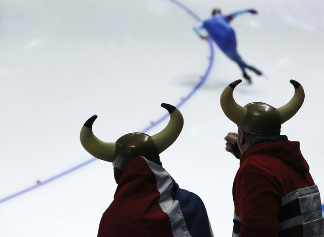 Two fans dressed as Vikings and draped in the Norwegian national flag watch of Henrik Fagerli Rukke of Norway, rear, compete during the men's 1,000 meters speedskating race at the Gangneung Oval at the 2018 Winter Olympics in Gangneung, South Korea, Friday, February 23, 2018. (Photo by John Locher/AP Photo)