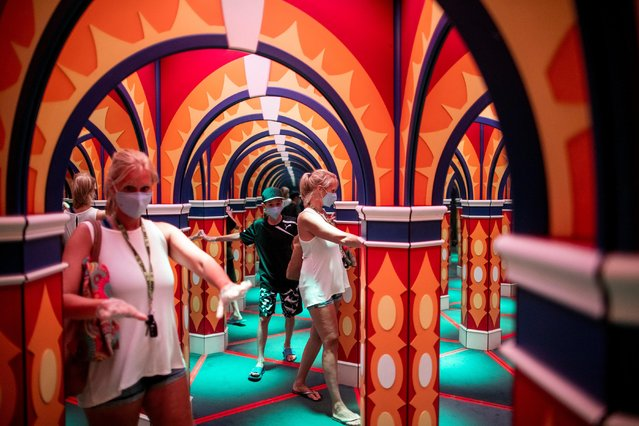 People walk through a house of mirrors attraction in Niagara Falls, Ontario, Canada on July 21, 2020. (Photo by Carlos Osorio/Reuters)