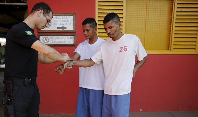 A warden removes handcuffs from Arlen Sena and Honorio Santos as they arrive to take part in the ACUDA programme at a complex of ten prisons in Porto Velho, Rondonia State, Brazil, August 27, 2015. (Photo by Nacho Doce/Reuters)