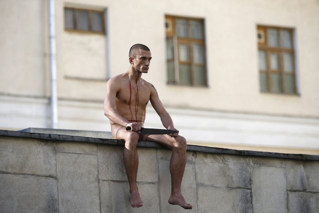 """Artist Pyotr Pavlensky sits on the wall enclosing the Serbsky State Scientific Center for Social and Forensic Psychiatry after he cut off a part of his earlobe during his protest action titled """"Segregation"""" in Moscow, in this October 19, 2014 file photo. (Photo by Maxim Zmeyev/Reuters)"""