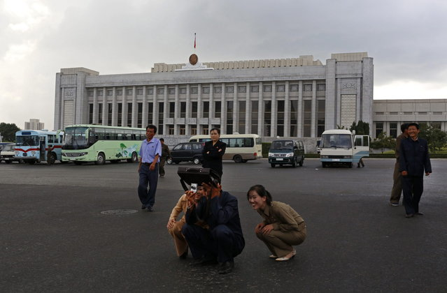 A North Korean woman reacts while her friend takes a picture in front of the Mansudae Assembly Hall in Pyongyang, North Korea Wednesday, September 19, 2012.  (Photo by Vincent Yu/AP Photo)