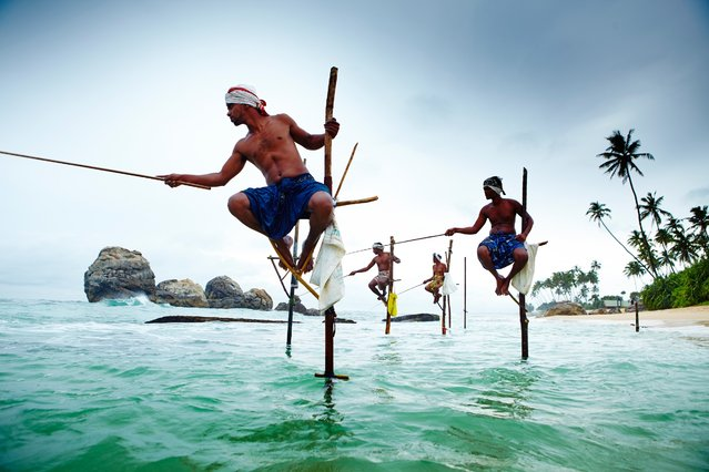 Stilt fisherman balance skillfully on poles while trying to catch their daily hauls in the crystal-clear Sri Lankan waters. (Photo by Matt Munro/Lonely Planet)