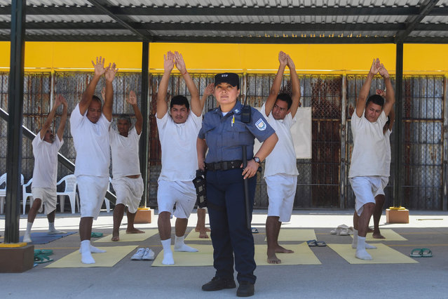 Nicol Gomez, 37, guardian at the La Esperanza prison poses for a portrait in front a group of prisoners practicing yoga in San Salvador, on March 4, 2018. (Photo by Marvin Recinos/AFP Photo)