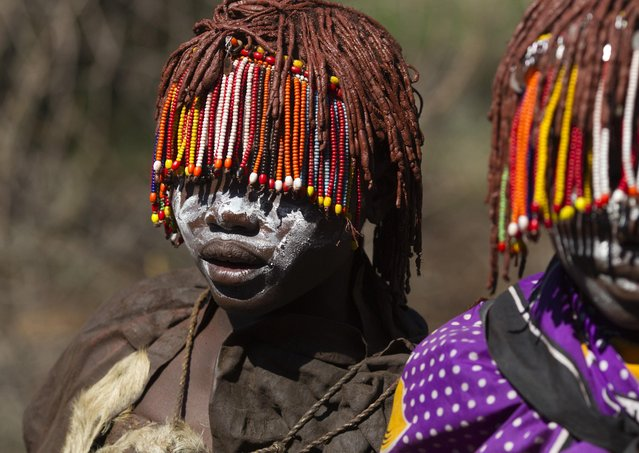 Pokot girls wearing beads and with their faces painted, walk towards a secluded place slightly more than a week prior to an initiation ceremony marking their passing over into womanhood, about 80 km (50 miles) from the town of Marigat in Baringo County November 25, 2014. (Photo by Siegfried Modola/Reuters)