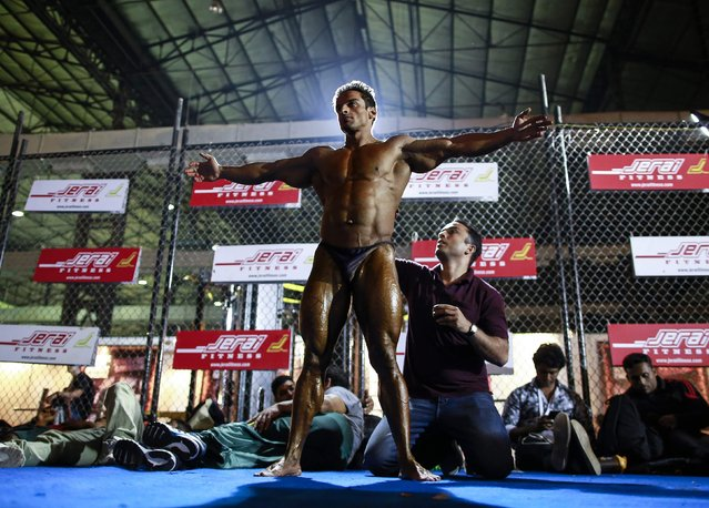 A participant has tanning lotion applied on his body during 6th World Body Building and Physique Sports competition in Mumbai December 9, 2014. (Photo by Danish Siddiqui/Reuters)