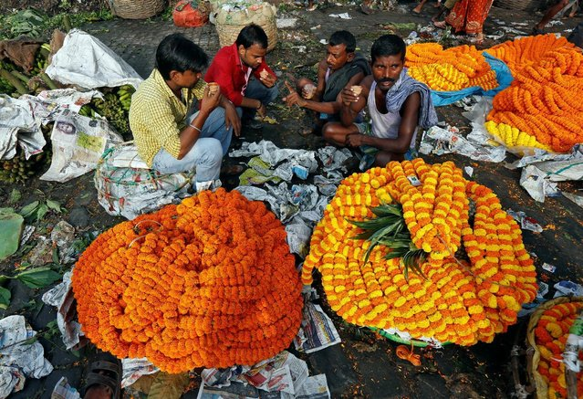 Vendors selling marigold garlands, which are used to decorate temples and homes during the Hindu festival of Durga Puja, drink tea as they wait for customers at a wholesale flower market in Kolkata, India October 6, 2016. (Photo by Rupak De Chowdhuri/Reuters)