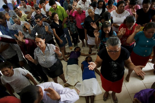 People pray during a mass in an evangelical church in the village of Rio Pardo next to Bom Futuro National Forest, in the district of Porto Velho, Rondonia State, Brazil, August 30, 2015. (Photo by Nacho Doce/Reuters)