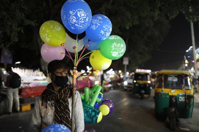 A balloon seller wearing a face mask as a precaution against coronavirus waits for customers in New Delhi India, Saturday, November 7, 2020. (Photo by Rajesh Kumar Singh/AP Photo)