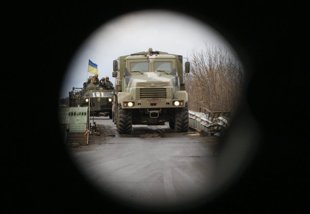 An Ukrainian military convoy is pictured through the shooting spot of an armored personnel carrier (APC) on the road from Kramatorsk to Debaltseve in Donetsk region, December 24, 2014. (Photo by Valentyn Ogirenko/Reuters)