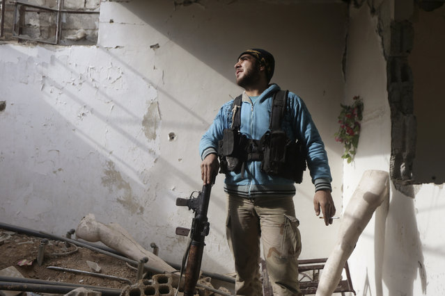 A rebel fighter from the Free Syrian Army's Al Rahman legion smokes a cigarette as he stands with his weapon inside a damaged room in Jobar, a suburb of Damascus, December 22, 2014. (Photo by Bassam Khabieh/Reuters)