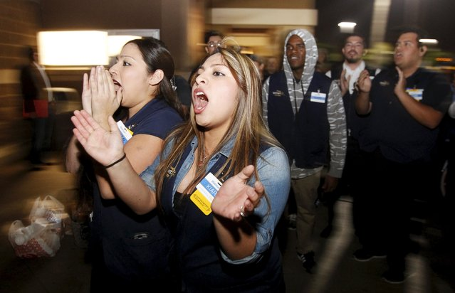 Current Walmart employees yell out that they love their jobs to former employees, who want a $15 per hour minimum wage and their jobs back, during a protest march at the store leading up to Black Friday in Pico Rivera, California November 19, 2015. (Photo by Alex Gallardo/Reuters)