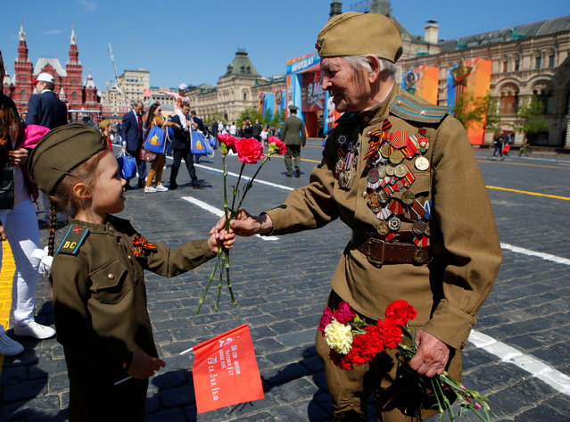 A veteran receives a red rose from a girl during the Victory Day celebrations in Moscow, Russia on May 09, 2018. (Photo by Sergei Karpukhin/Reuters)