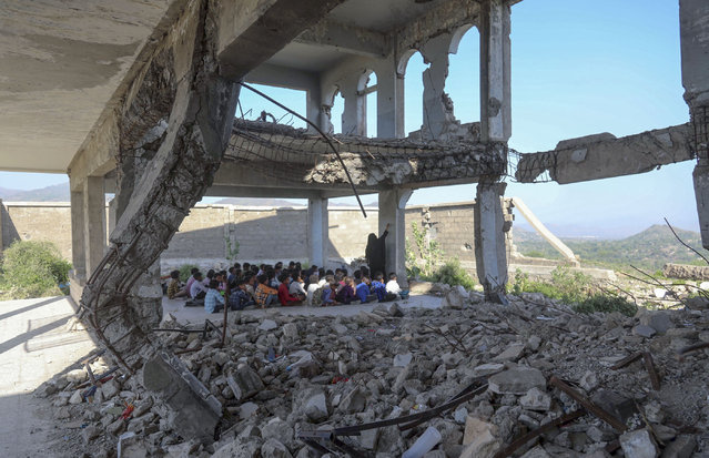 Yemeni pupils attend class on the first day of the new academic year, in a makeshift classroom in their school compound which was heavily damaged two years ago in an air strike, in the country's third-city of Taez on October 7, 2020. (Photo by Ahmad Al-Basha/AFP Photo)