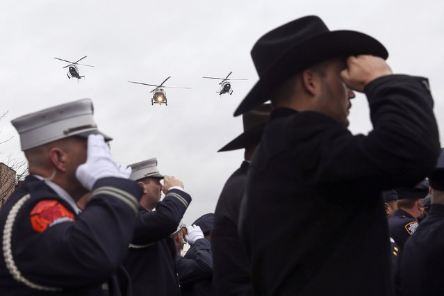 NYPD police helicopters fly over the funeral procession for NYPD officer Wenjian Liu as law enforcement officers salute in the Brooklyn borough of New York January 4, 2015. (Photo by Shannon Stapleton/Reuters)