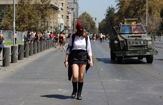 A woman walks next to riot police vehicle during a women's strike as part of International Women's Day activities in Santiago, Chile on March 9, 2020. (Photo by Sofia Yanjari/Reuters)