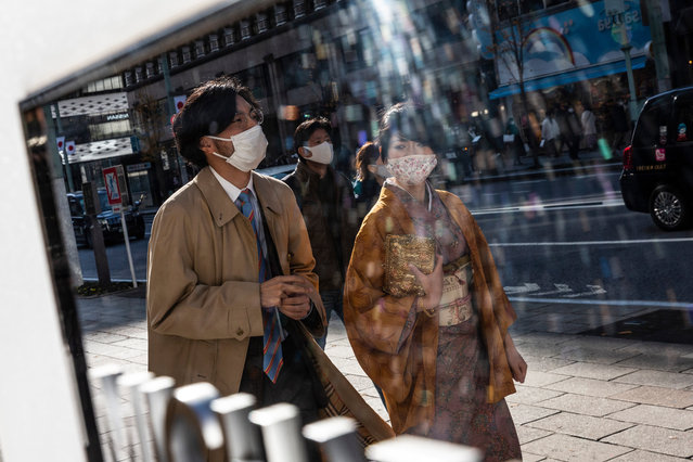People wearing face masks walk through Ginza area on December 27, 2020 in Tokyo, Japan. Japan announced it will close its borders to non-resident foreign nationals from tomorrow until the end of January after two people were discovered to be infected with a new strain of Covid-19 coronavirus that has begun spreading around the world. The country is also grappling with a surge in coronavirus infections, with Tokyo reporting 708 cases today. To date, Japan has recorded 218,453 infections, 3,052 deaths and 3,052 recoveries from the virus. (Photo by Yuichi Yamazaki/Getty Images)