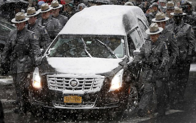 The hearse carrying the casket of former New York Governor Mario Cuomo is escorted by members of the New York State Police as it arrives at St. Ignatius Loyola Church for funeral service in the Manhattan borough of New York January 6, 2015. (Photo by Brendan McDermid/Reuters)