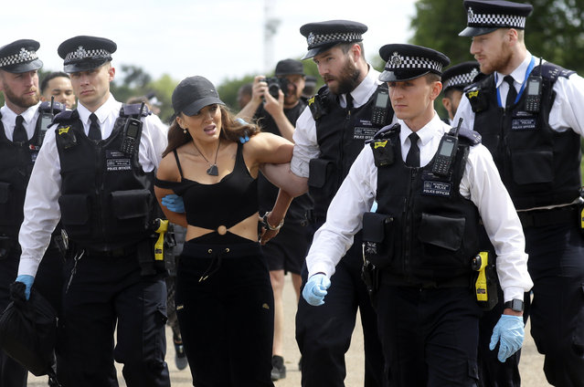 A woman is arrested during a mass gathering protest organised by the group called 'UK Freedom Movement', in Hyde Park in London as the country is in lockdown to help stop the spread of coronavirus, Saturday, May 16, 2020. The group claims that the coronavirus lockdown is illegal. (Photo by Kirsty Wigglesworth/AP Photo)