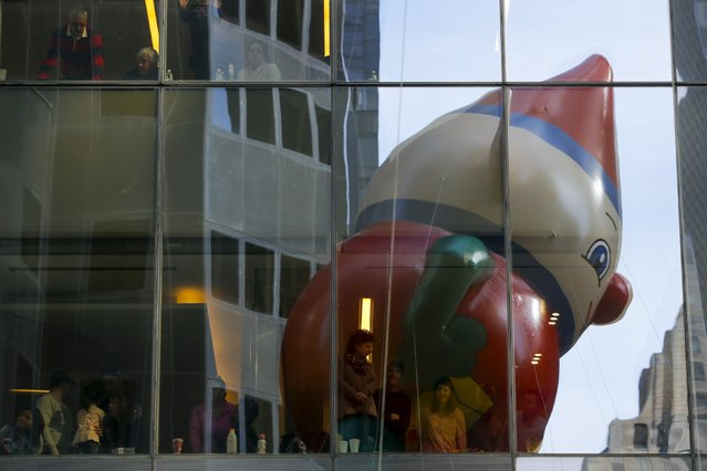 A Macy's Elf balloon passes people in windows during the 89th Macy's Thanksgiving Day Parade in the Manhattan borough of New York, November 26, 2015. (Photo by Andrew Kelly/Reuters)