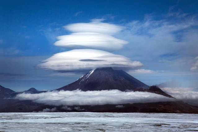 Lenticular clouds hover of the mountains of the Kamchatka Peninsula in Russia. (Photo by Denis Budkov/Caters News)
