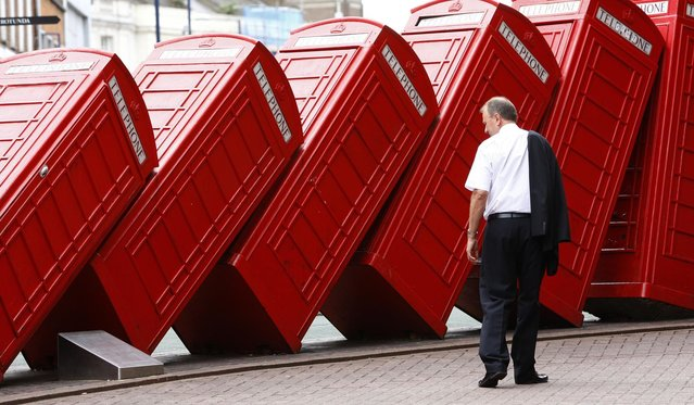 A piece by artist David Mach and entitled 'Out of Order' shows a row of traditional English red phone boxes in Kingston, south of London July 15, 2008. (Photo by Eddie Keogh/Reuters)