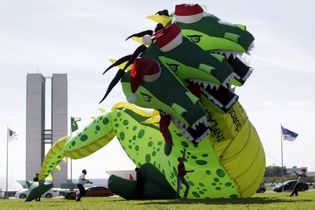 "A giant inflatable model in the shape of a thirteen meters high, three-headed dragon is seen during a protest against inflation, unemployment and high interest rates in front of the National Congress in Brasilia, Brazil December 2, 2015. The signs on the dragon read (L-R) ""Inflation, high interest rates, unemployment"". (Photo by Ueslei Marcelino/Reuters)"